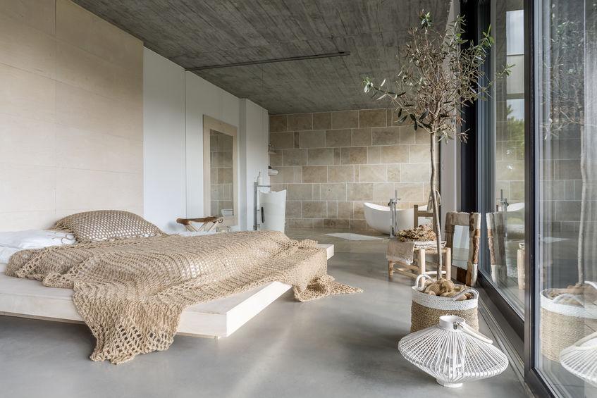 Camera da letto contemporanea con arredi naturali e colori neutri