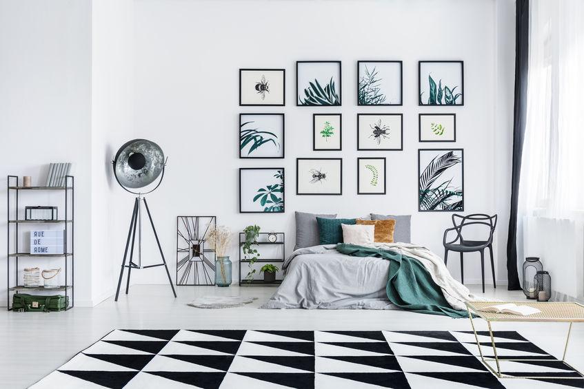 Casa trendy: composizione di cornici sulla parete del letto