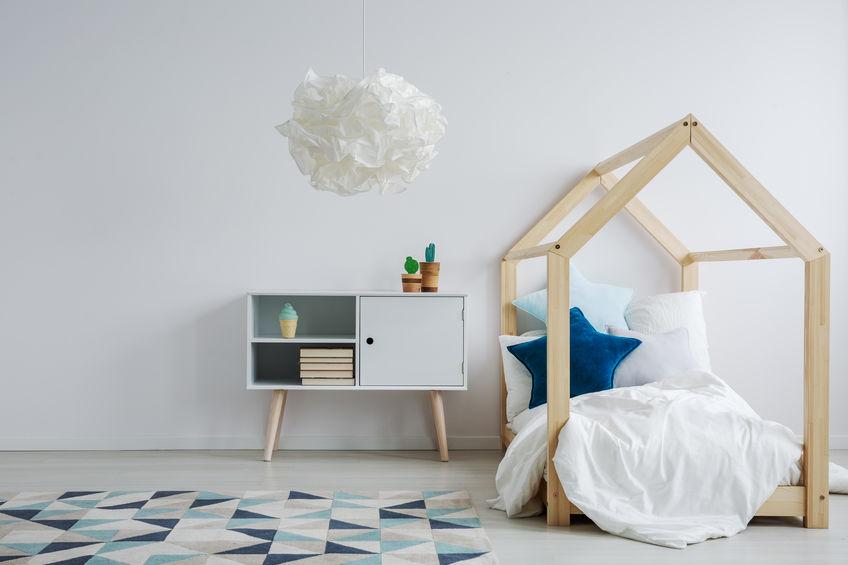 Zona letto montessoriana: futon e comodino nella camera del bambino